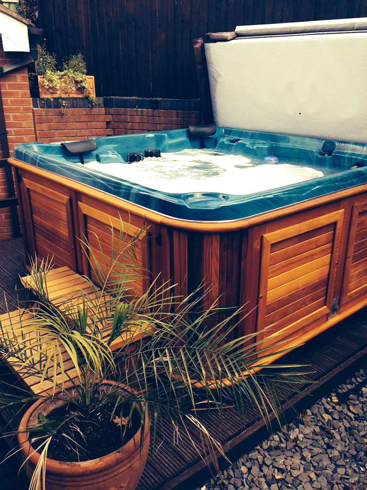 Arctic Spas hot tub in red cedar cabinet in a patio