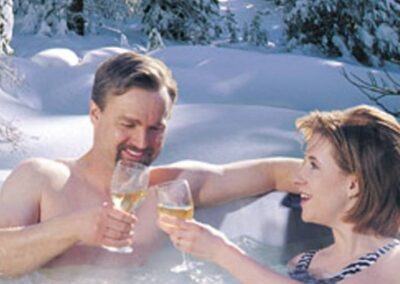 Celebrating couple in an Arctic Spas hot tub in winter