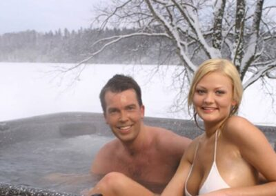 Smiling couple in an Arctic Spas hot tub in winter