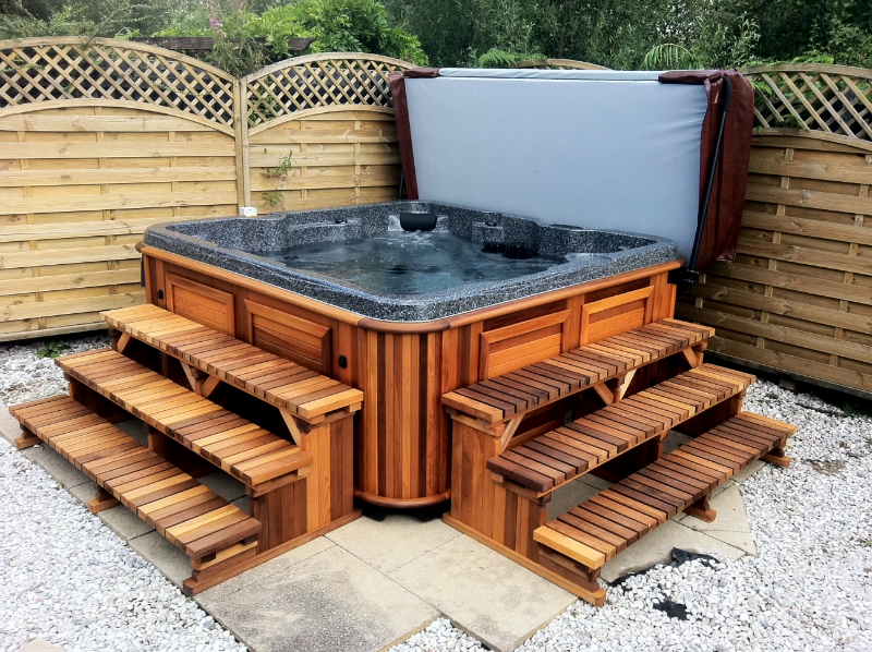 Arctic Spas hot tub in red cedar cabinet with two side stairs