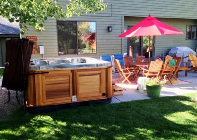 Arctic Spas hot tub in red cedar cabinet in the backyard