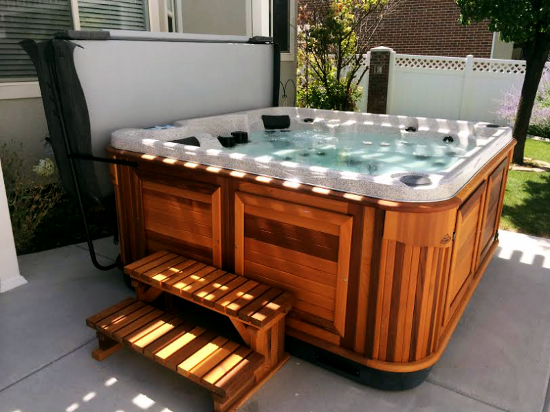 Arctic Spas hot tub with a red cedar cabinet in the backyard
